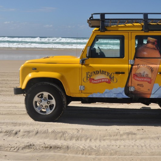Four wheel drive on beach with Bundaberg Brewed Drinks advertised on side